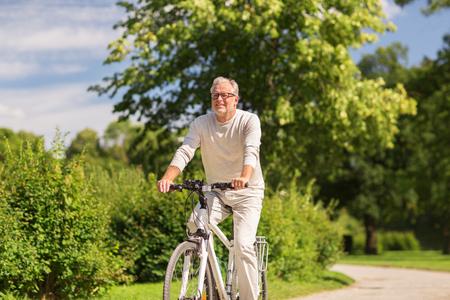 gelukkige senior man fietsten in zomer park