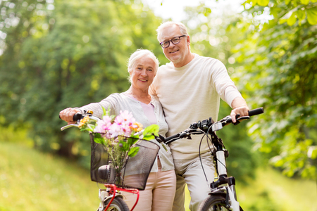 happy senior couple with bicycles at summer park Imagens