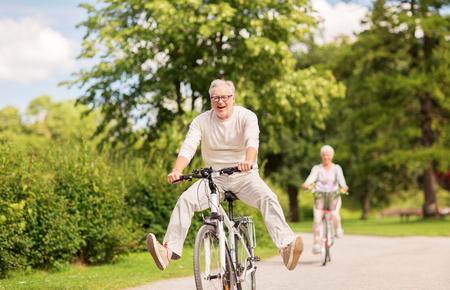 Gelukkig senior paar fietsen in het zomerpark Stockfoto