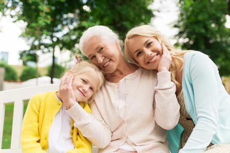 notion de famille, de génération et de personnes - heureuse femme souriante avec fille et senior mère assise sur le banc de parc
