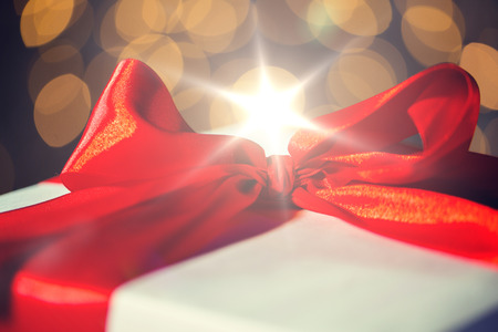 close up of christmas gift with bow over lights Stock Photo