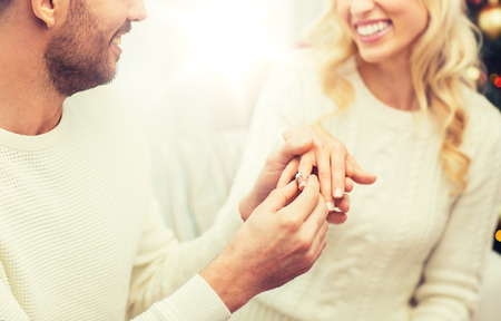 love, couple, relationship and holidays concept - happy man giving diamond ring to woman for christmas Stock Photo
