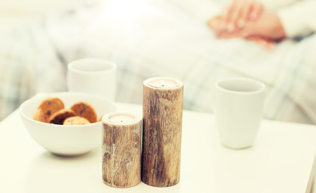 christmas, winter, holidays and concept - close up of candles, cookies and tea cups on table over family couple
