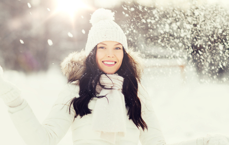 people, season and leisure concept - happy woman with snow outdoors in winter