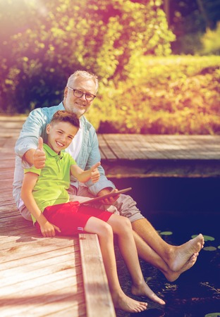 grandfather and boy with tablet pc on river berth Stock Photo