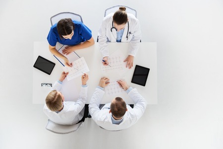 medicine, healthcare and cardiology concept - group of doctors with cardiograms, clipboard and tablet pc computers at hospital Stock Photo