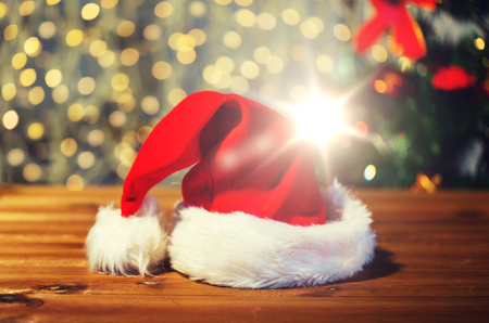 close up of santa hat on wooden table over lights Stock Photo