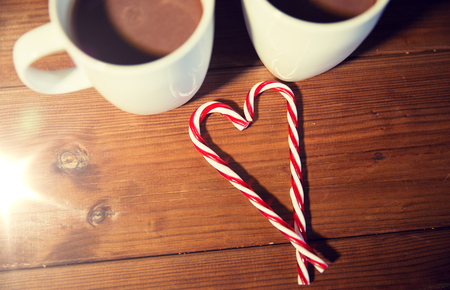 christmas candy canes and cups on wooden table Stock Photo