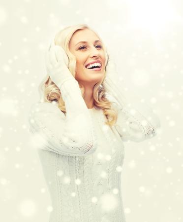 Sorridente giovane donna in inverno paraorecchie e maglione Archivio Fotografico - 85632200