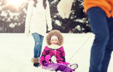 winter fashion: happy family with sled walking in winter forest Stock Photo