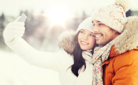 happy couple taking selfie by smartphone in winter Stock Photo