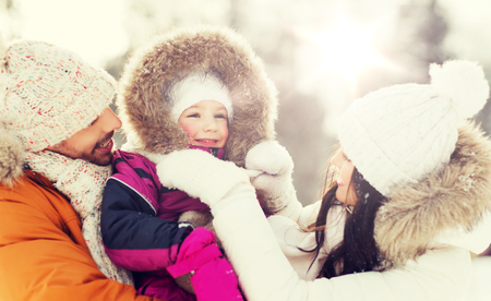 winter fashion: happy family with child in winter clothes outdoors