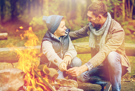 father and son roasting marshmallow over campfire Stock Photo