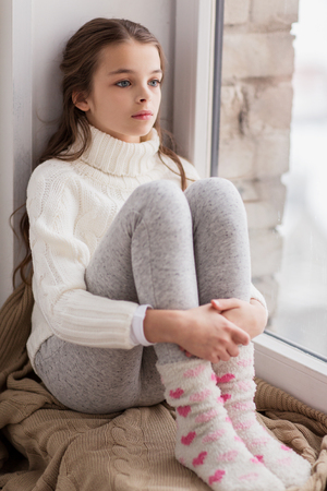 집 창문에서 겨울에 앉아 슬픈 소녀