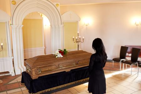 Verdrietige vrouw met kist bij begrafenis in de kerk