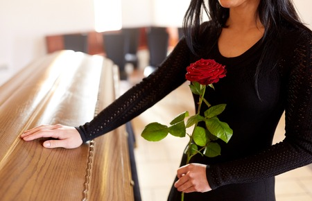 woman with red roses and coffin at funeral