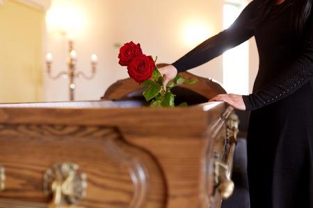 Vrouw met rode rozen en doodskist bij begrafenis Stockfoto