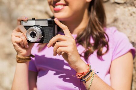 old photo: close up of woman with vintage camera outdoors