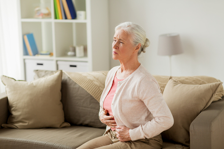 senior woman suffering from stomach ache at home