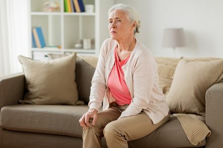 Senior donna che soffre di dolore in gamba a casa Archivio Fotografico - 85632285