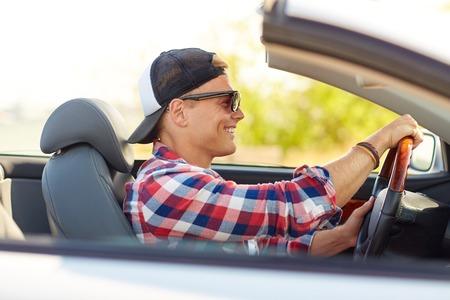 컨버터블 자동차를 운전하는 그늘에서 행복한 젊은이