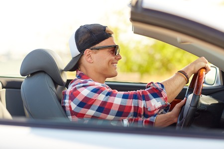 happy young man in shades driving convertible car