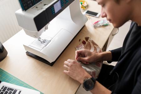 sewing machines: fashion designer with making dress at studio