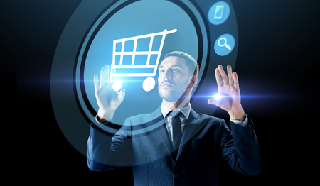 businessman with shopping cart on virtual screen Banque d'images