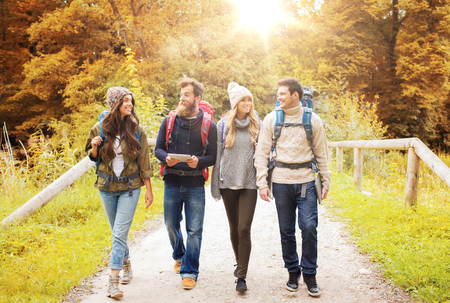 friends hiking with backpacks and tablet pc