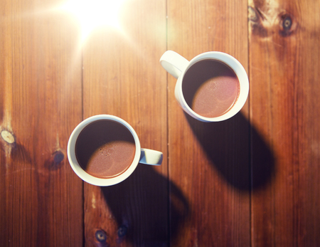 cups of hot chocolate or cocoa drinks on wood