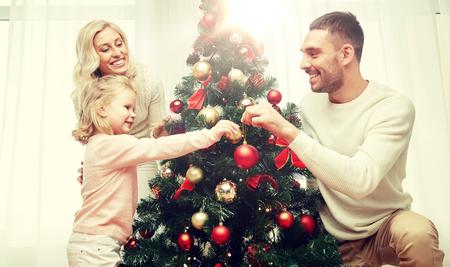 幸せな家族が自宅のクリスマス ツリーを飾る