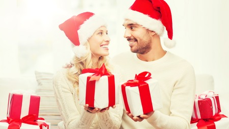 happy couple at home exchanging christmas gifts Banque d'images