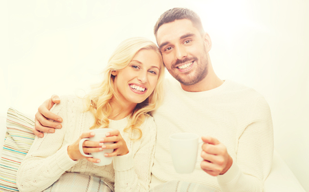 happy couple with cups drinking tea at home Banque d'images