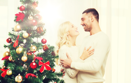 happy couple hugging near christmas tree at home Banque d'images
