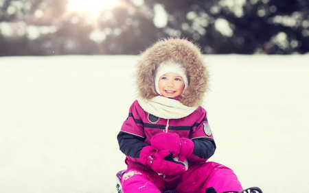 happy little kid on sled outdoors in winter Banque d'images