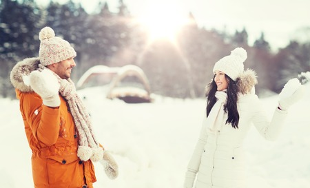 winter fashion: happy couple playing snowballs in winter