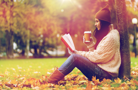 woman with book drinking coffee in autumn park Stock fotó