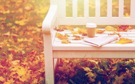 newspaper and coffee cup on bench in autumn park