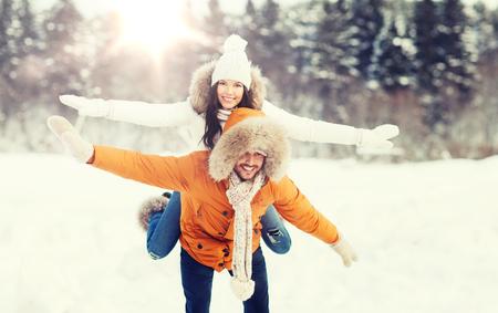 冬の背景の上楽しんで幸せなカップル 写真素材