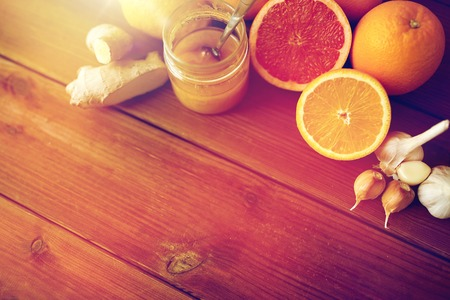 honey, citrus fruits, ginger and garlic on wood