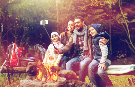 family with smartphone taking selfie near campfire Banque d'images