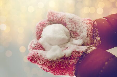 close up of woman holding snowball outdoors
