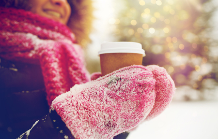 close up of hand with coffee outdoors in winter