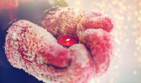 촛불을 들고 겨울 장갑에 손을 가까이