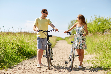happy couple with bicycles on country road Banque d'images