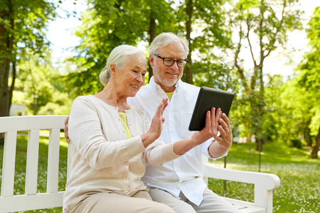 happy senior couple with tablet pc at summer park