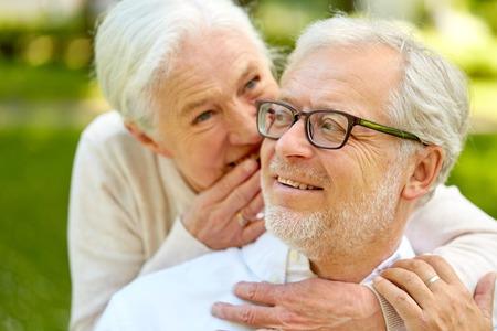 close up of senior couple whispering outdoors