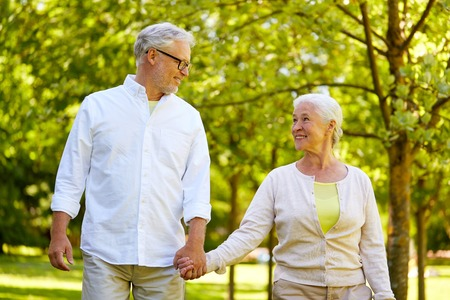 happy senior couple walking at summer park