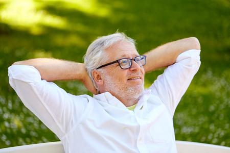 happy senior man in glasses sitting at summer park Banque d'images