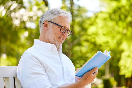 happy senior man reading book at summer park
